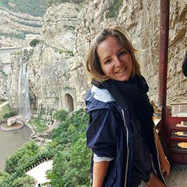 Chica asomada a un balcón en una montaña